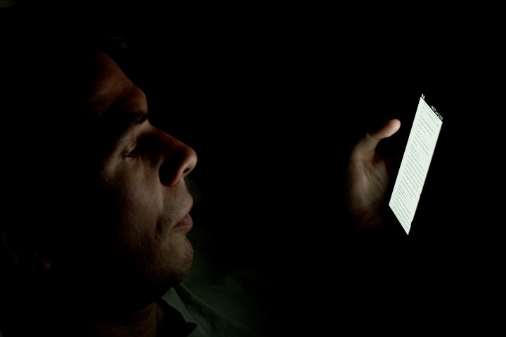 Person_looking_at_smartphone_in_the_dark_(2)