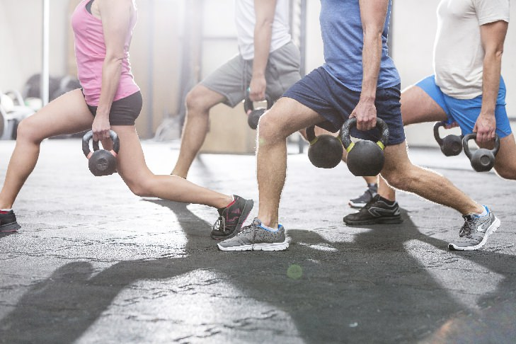 people-with-lean-legs-exercising-with-kettlebell