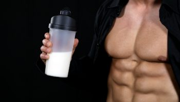 Bodybuilder holding creatine powder